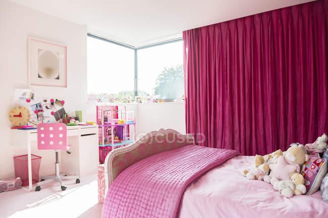 Rosa dormitorio de la niña en el interior durante el día - foto de stock