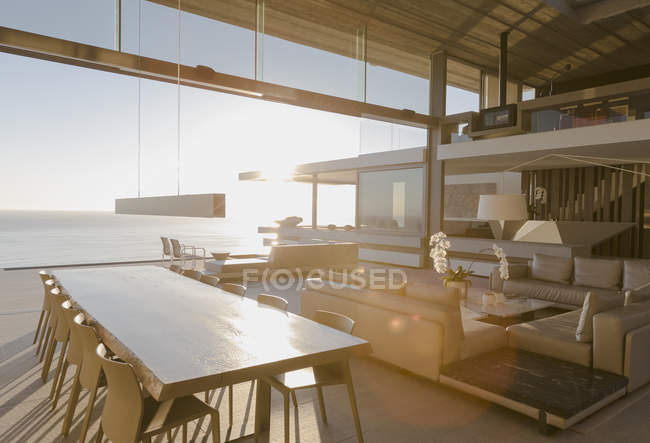 Sunny modern, luxury home showcase interior dining room and living room with ocean view — Stock Photo