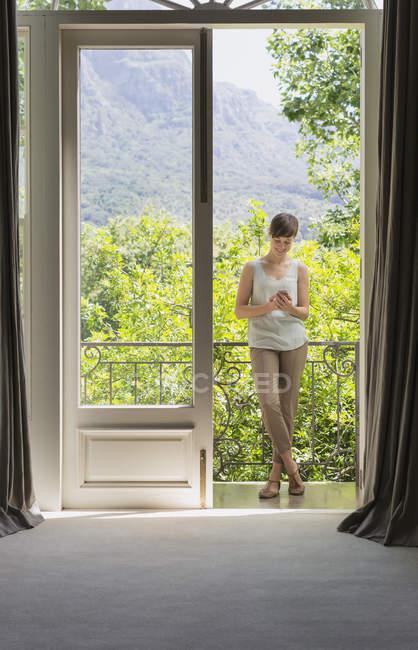 Жінка, стоячи на терасі на розкішний сучасний будинок — стокове фото