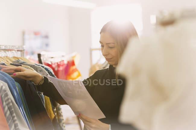 Покупатель моды рассматривает документы на стойках для одежды — стоковое фото