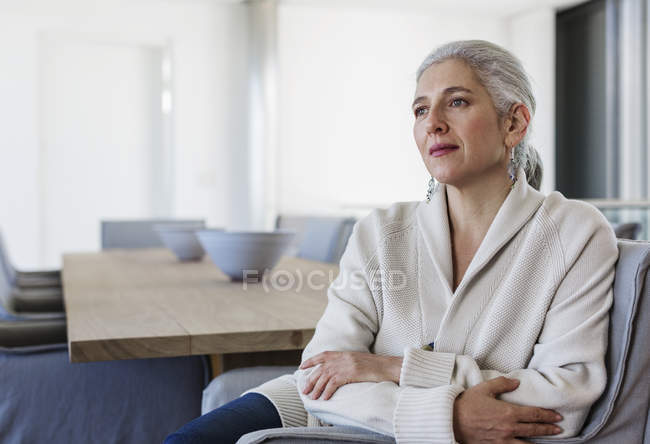 Serious, pensive mature woman at dining table looking away — Stock Photo
