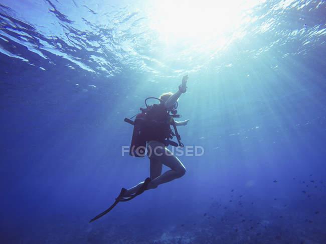 Scuba diver subacqueo sotto i raggi del sole — Foto stock