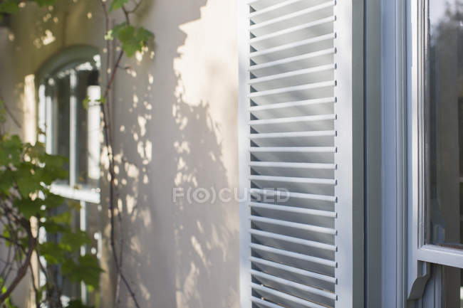 Sun shining on house shutters — Stock Photo