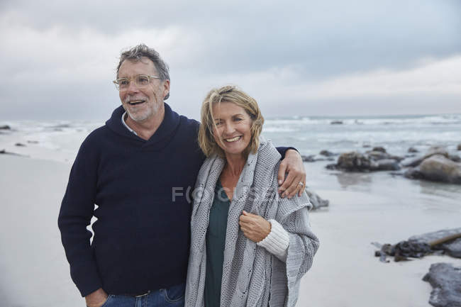 Portrait smiling senior couple hugging on stormy beach — Stock Photo