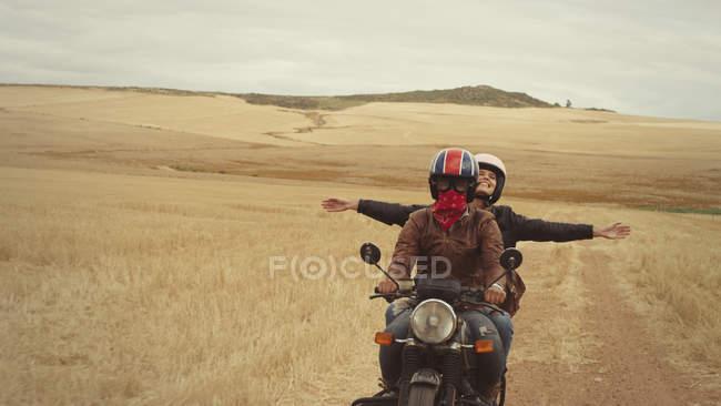 Mulher jovem exuberante moto na paisagem rural — Fotografia de Stock