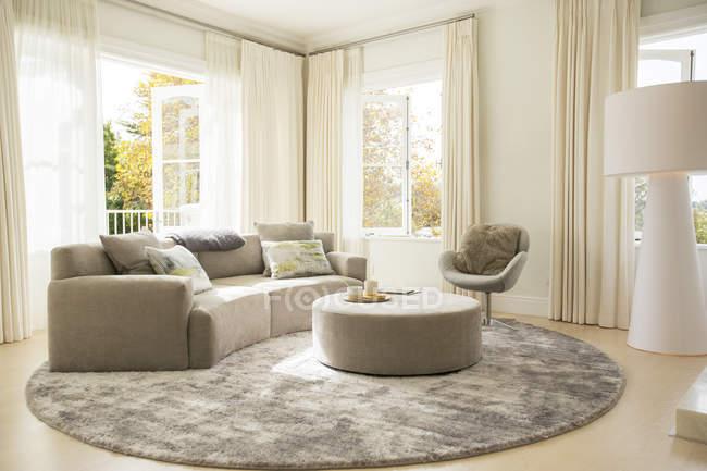 Tappeto rotondo sotto divano e pouf in salotto — Foto stock