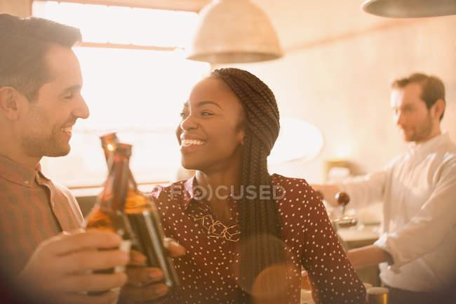 Sorrindo casal brindar garrafas de cerveja no bar — Fotografia de Stock
