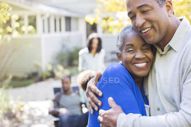 Primer plano retrato de feliz pareja de ancianos abrazándose en el patio - foto de stock
