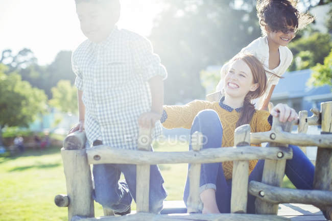 Babysitter and children playing outdoors — Stock Photo
