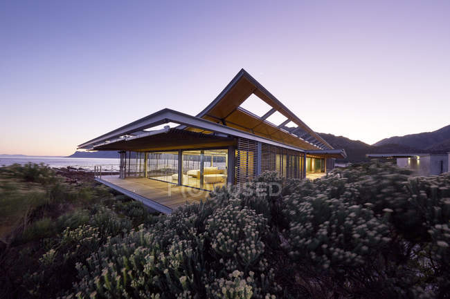 Casa de luxo moderna com vista para o mar ao entardecer — Fotografia de Stock