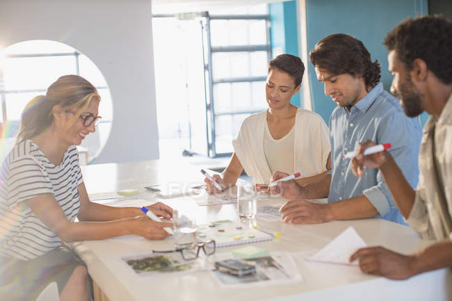 Creative business people brainstorming, drawing in conference room meeting — Stock Photo