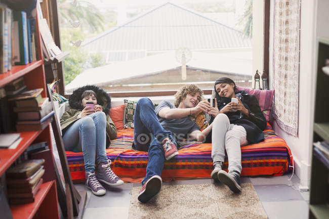 Young friends hanging out using cell phones in apartment window — Stock Photo
