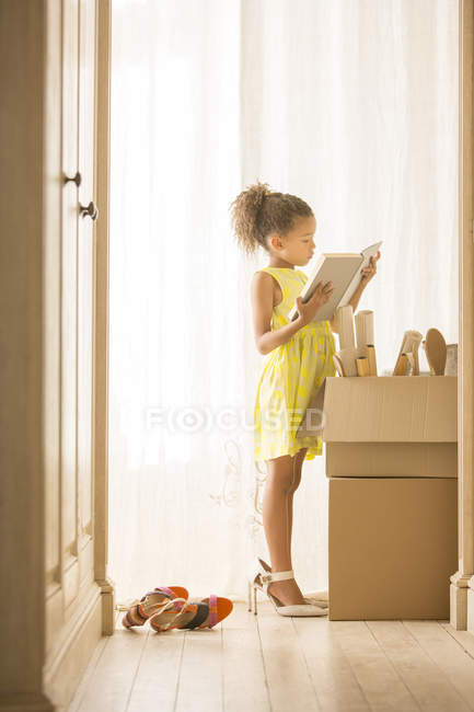 Young girl looking through moving boxes — Stock Photo