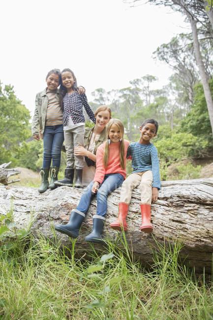Ученики и учитель улыбаются на деревянном бревне — стоковое фото