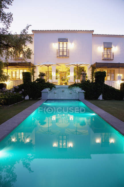 Lap pool and Spanish villa at dusk — Stock Photo
