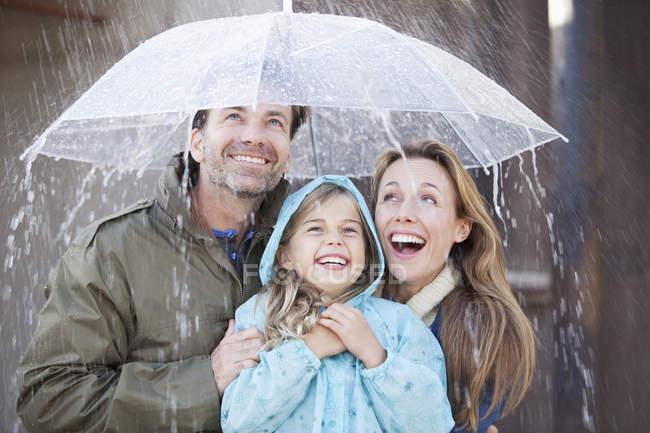 Famille enthousiaste sous parapluie en averse — Photo de stock
