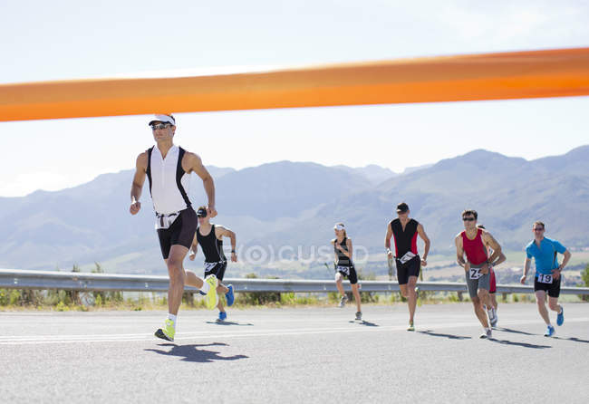 Runners crossing race finish line — Stock Photo