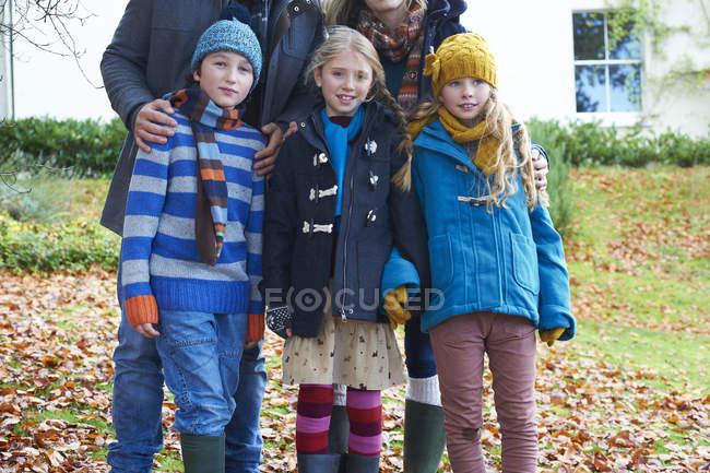 Дети улыбаются вместе осенними листьями — стоковое фото