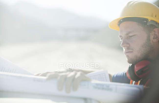 Worker reading blueprints in quarry — Stock Photo