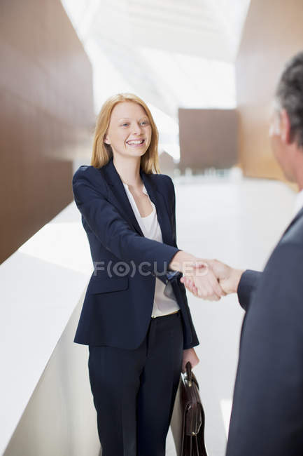 Smiling businesswoman shaking hands with businessman — Stock Photo