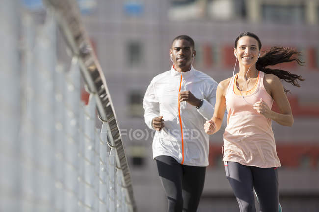 Friends running through city streets together — Stock Photo