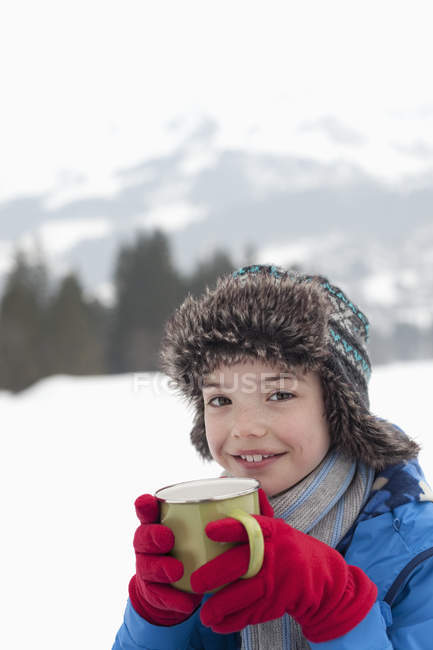 Portrait of smiling boy drinking hot chocolate in snowy field — Stock Photo