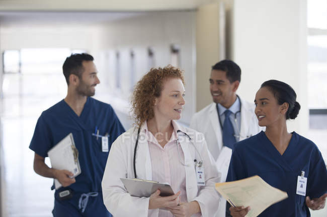 Hospital staff talking in modern hallway — Stock Photo