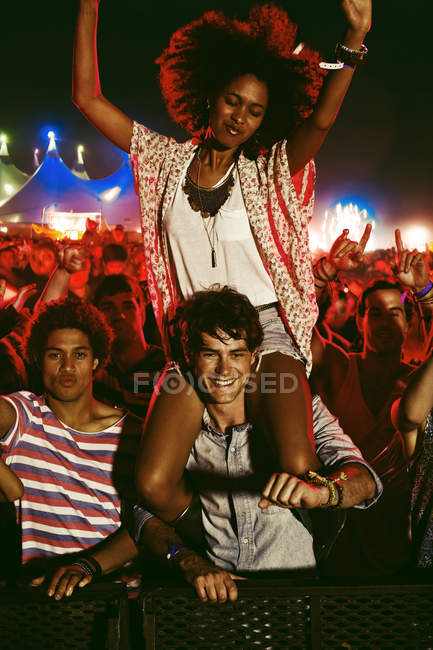 Cheering woman on man?s shoulders at music festival — Stock Photo