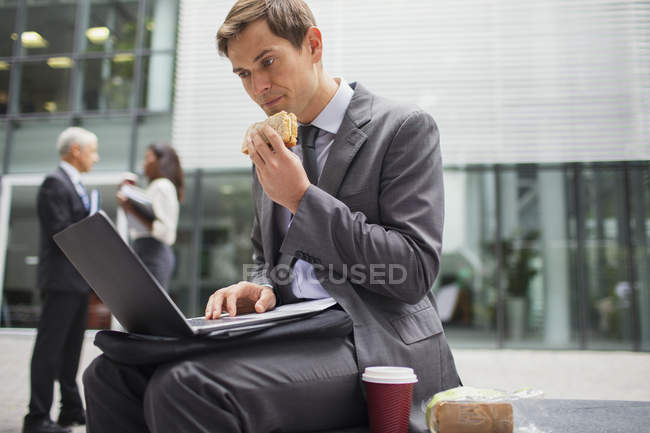 Businessman eating lunch while working outside office building — Stock Photo