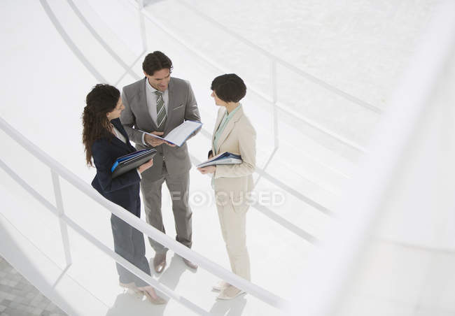 Business people reviewing paperwork on walkway — Stock Photo