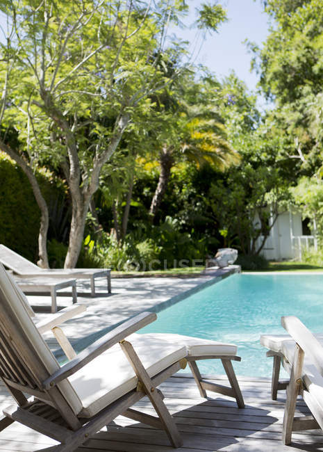 Lawn chairs and swimming pool in backyard — Stock Photo
