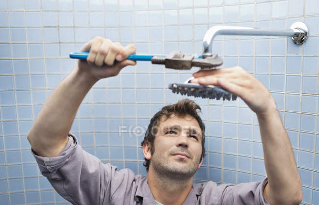 Plumber working on shower head in bathroom — Stock Photo