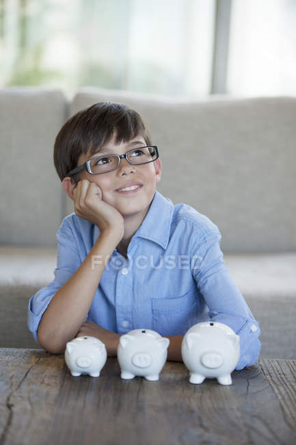 Boy sitting with piggy banks at coffee table — Stockfoto