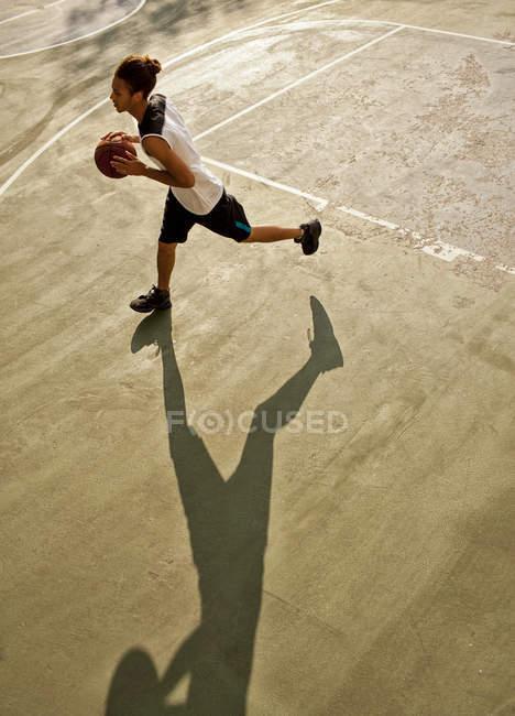 Мужчина играет в баскетбол на площадке — стоковое фото