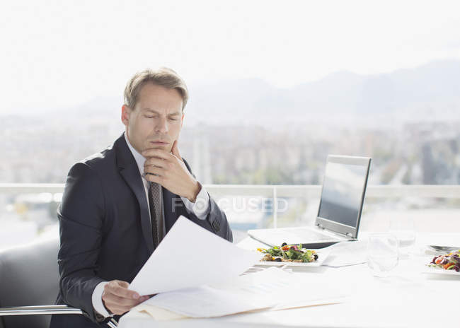 Businessman with lunch reviewing paperwork — Stock Photo