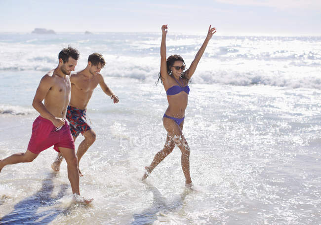 Enthusiastic friends running and splashing in ocean — Stock Photo