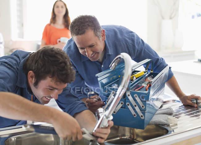 Умелые кавказские водопроводчики, работающие на кухонной раковине — стоковое фото