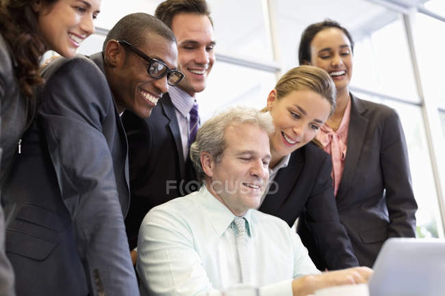 Smiling business people sharing laptop in meeting at modern office — Stock Photo