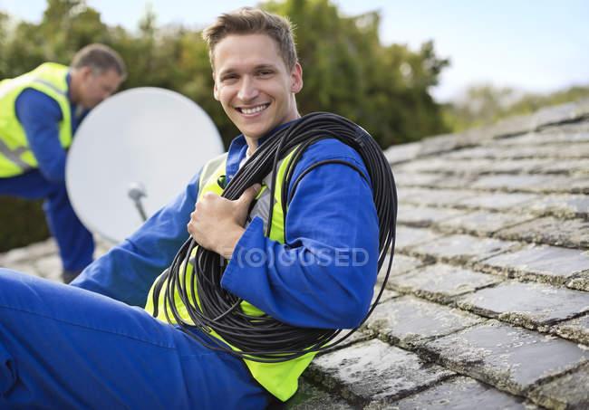 Умелые кавказские рабочие устанавливают спутниковую тарелку на крыше — стоковое фото