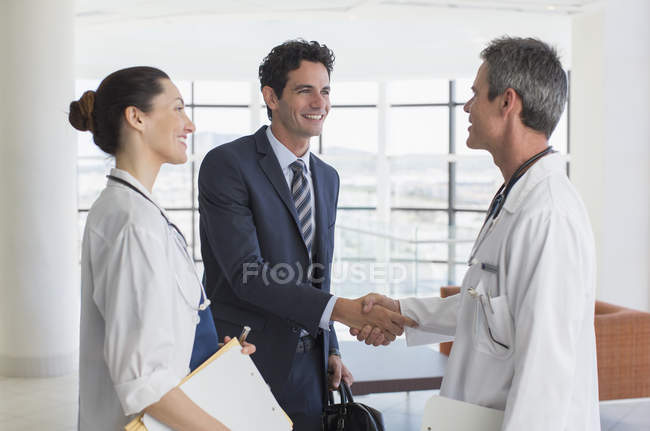 Doctor and businessman handshaking in hospital lobby — Stock Photo