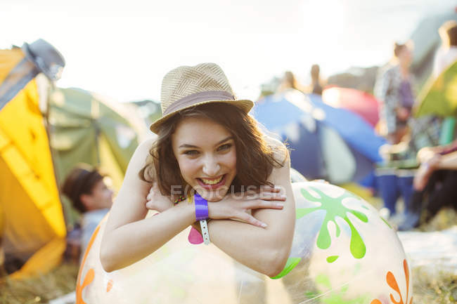 Portrait of smiling woman leaning on inflatable chair outside tents at music festival — Stockfoto