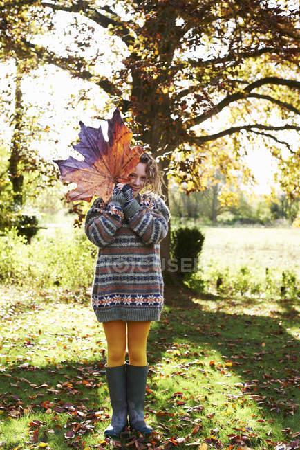 Девочка играет с осенних листьев на открытом воздухе — стоковое фото