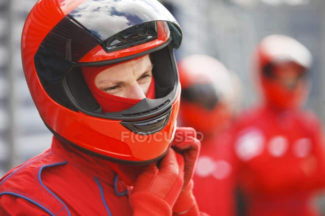 Гонщик завязывает шлем на трассе — стоковое фото