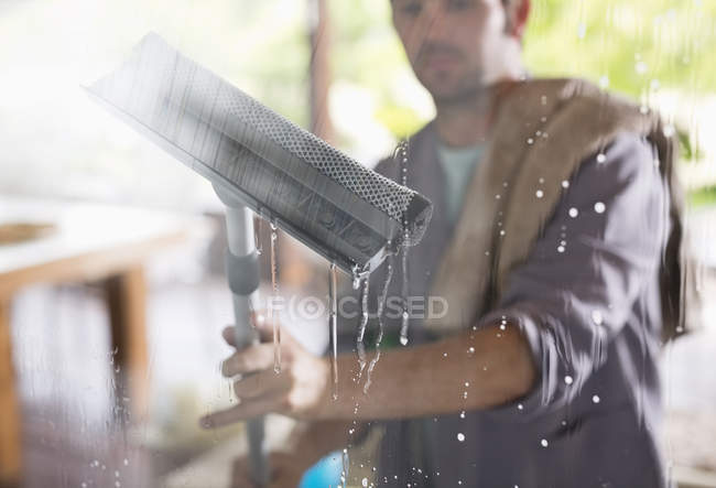 Skillful caucasian man washing window with squeegee — Stock Photo