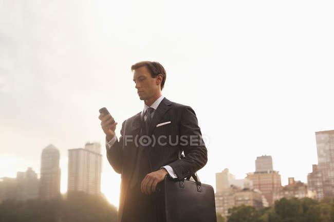 Uomo d'affari che utilizza il cellulare nel parco urbano — Foto stock