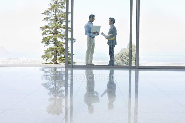 Vista laterale di uomini d'affari che parlano in ufficio moderno — Foto stock