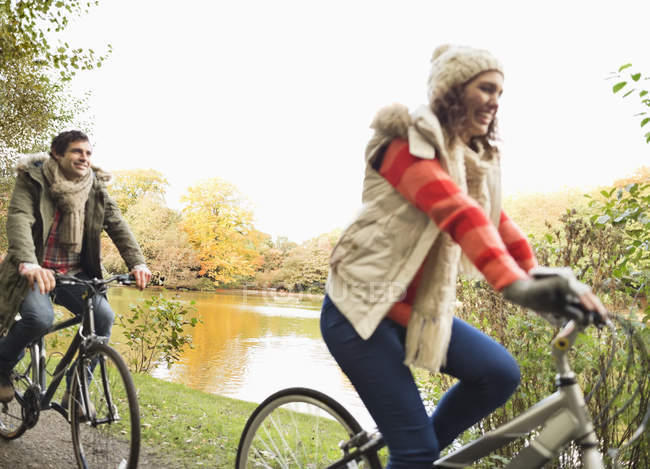 Happy couple riding bicycles in park — Stock Photo
