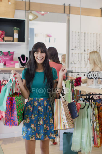 Woman carrying shopping bags in clothing store — Stock Photo