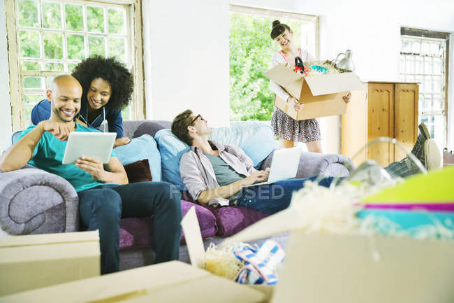 Young happy friends relaxing together in new home — Stock Photo