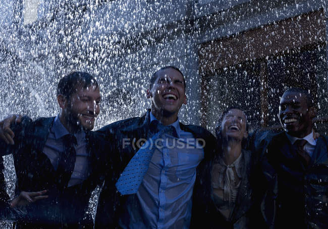 Happy multiracial rnthusiastic businessmen in rain — Stock Photo